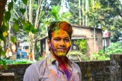 Zbliżenie strzał zakrywający z wielo- koloru suchą farbą przy Holi festiwalem Indiański młody człowiek obraz royalty free