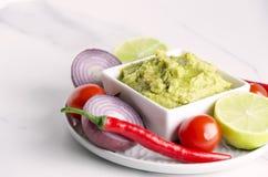 Zbliżenie talerz z różnymi składnikami, warzywami i pucharem z świeżym smakowitym guacamole na bielu stole, fotografia royalty free