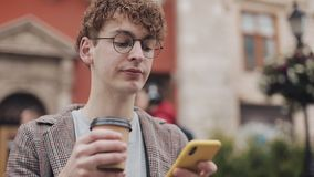 Zbliż się do młodego hipsterza w okularach i kurtce, używając smartfona i pijąc kawę siedząc na ławce zbiory wideo