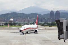 Zbliżać się samolot z jetbridge w Taipei shanu Pieśniowym lotnisku Zdjęcie Royalty Free