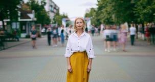 Zbliża wewnątrz czasu upływ dojrzała blondynki pozycja w miasto ulicie na letnim dniu zbiory wideo