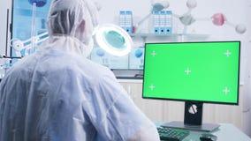Zbliża wewnątrz strzelał badacz pracuje z zieleń ekranu monitorem zdjęcie wideo
