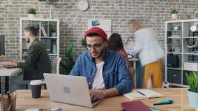 Zbliża wewnątrz upływ pracuje w biurowym używa laptopie przy biurkiem kreatywnie facet zbiory