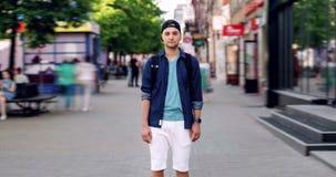Zbliża za czasu upływie atrakcyjny facet stoi outdoors w ulicie z plecakiem zdjęcie wideo