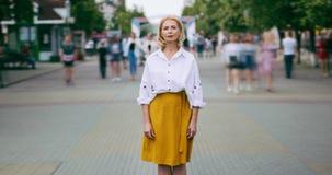 Zbliża za czasu upływie dosyć dojrzała kobieta patrzeje kamery pozycję w ulicie zbiory wideo