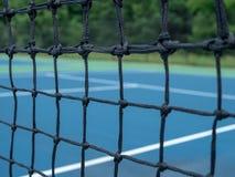 Zbliżający widok tenisowego sądu sieci siatka z rozmytymi sądami w tle obraz royalty free