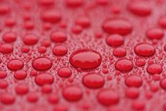 Zbliżeń waterdrops na czerwonej ceramicznej pokrytej farbie ukazują się obraz stock