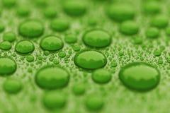 Zbliżeń waterdrops na zielonej ceramicznej pokrytej farbie ukazują się obraz stock