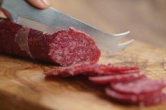 Zbliżenia żeńskiego przecinania salami cienka kiełbasa Obrazy Royalty Free