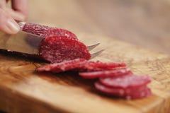 Zbliżenia żeńskiego przecinania salami cienka kiełbasa Zdjęcia Royalty Free