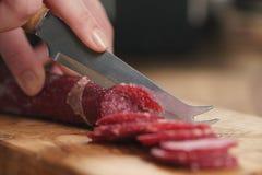 Zbliżenia żeńskiego przecinania salami cienka kiełbasa Fotografia Royalty Free