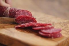 Zbliżenia żeńskiego przecinania salami cienka kiełbasa Obraz Royalty Free