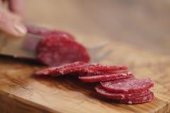 Zbliżenia żeńskiego przecinania salami cienka kiełbasa Fotografia Stock