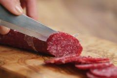 Zbliżenia żeńskiego przecinania salami cienka kiełbasa Zdjęcie Stock