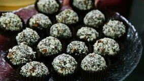Zbliżenia ciasteczko wręcza stawiających czekoladowych cukierki na round talerzu zbiory wideo