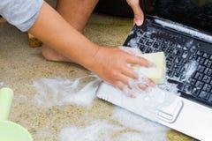 Zbliżenia cleaning komputerowy notatnik z naczynia domycia mydłem, techn Obraz Stock