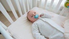 Zbliżenia dolly strzał śliczny 3 miesiąca starego chłopiec lying on the beach w łóżku z zabawkarskim carousel zdjęcie wideo