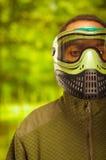 Zbliżenia headshot mężczyzna jest ubranym kurtki, zielonej i czarnej ochrony twarzową maskową trwanie okładzinową kamerę, lasowy  Zdjęcie Royalty Free