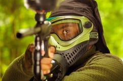 Zbliżenia headshot mężczyzna jest ubranym zielonej i czarnej ochrony twarzową maskową okładzinową kamerę wskazuje paintball pisto Zdjęcia Stock