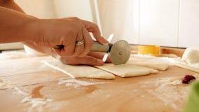 Zbliżenia 4k materiał filmowy kobieta wręcza trzymać wokoło krajacza nożowego tnącego ciasta na drewnianym kuchennym countertop zdjęcie wideo