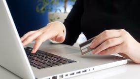 Zbliżenia 4k materiał filmowy pracuje na laptopie i trzyma kredytową kartę w ręce młody bizneswoman zdjęcie wideo