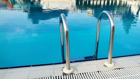 Zbliżenia 4k wideo metal drabina przy pustym pływackim basenem przy hotelowym kurortem zbiory wideo