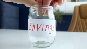 Zbliżenia 4k wideo rodzinna miotanie metalu moneta w szklanym słoju Pojęcie pieniędzy savings i rodzinny budżet zbiory wideo