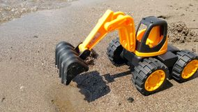 Zbliżenia 4k wideo zabawkarska pomarańczowa ekskawator pozycja na piaska morza plaży zbiory wideo