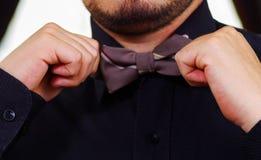 Zbliżenia man& x27; s klatka piersiowa jest ubranym białą koszula, wiąże bowtie używać rękę, twarz częsciowo widoczna, mężczyzna  Obrazy Royalty Free