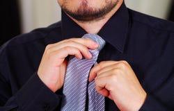 Zbliżenia man& x27; s klatka piersiowa jest ubranym białą koszula, wiąże krawat używać rękę, twarz częsciowo widoczna, mężczyzna  Obrazy Royalty Free