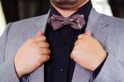 Zbliżenia man& x27; s klatki piersiowej teren jest ubranym formalnego kostium i bowtie przystosowywa kurtka kołnierz, używać rękę Obraz Royalty Free