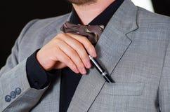 Zbliżenia man& x27; s klatki piersiowej teren jest ubranym formalnego kostium i krawat umieszcza pióro w kurtki kieszeni, mężczyz Fotografia Stock