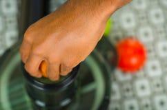 Zbliżenia man& x27; s wręcza używać soku producenta, wkłada marchewki w maszynę, zdrowy stylu życia pojęcie Zdjęcie Stock