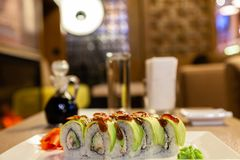 Zbliżenia shogun suszi rolka z avocado, truskawka, teriyaki kumberland, sezam, wasabi, imbir, biały japończyka talerz, soja kumbe zdjęcia stock