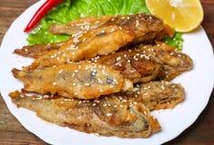 Zbliżenia talerz z hiszpańskimi boquerones fritos, obijać i smażyć sardelami typowymi w Hiszpania, na nieociosanym drewnianym sto Zdjęcia Stock
