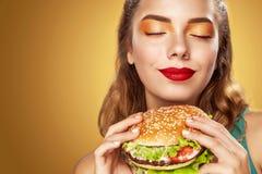 zbliżenia twarzy portreta kobieta Piękna blond młoda kobieta ma zabawę je dużego hamburger Reklama dla kawiarni obrazy stock