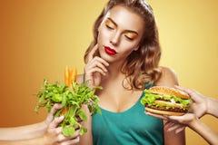 zbliżenia twarzy portreta kobieta Piękna blond młoda kobieta wybiera między hamburgerem i jarosza jedzeniem zdjęcia royalty free
