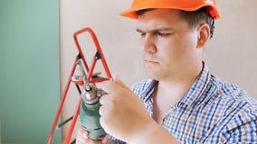 Zbliżenia zwolnionego tempa wideo uśmiechnięty męski pracownika ir budowniczy wkłada świderu kawałek i patrzeje in camera w czerw zbiory wideo