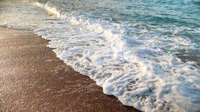 Zbliżenia zwolnionego tempa wideo wirować wodę morską po fal miażdży na brzeg przy zmierzchem i gotować się zdjęcie wideo