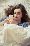 Zbliżenie ładny nastoletniej dziewczyny lying on the beach w łóżku patrzeć jej telefon komórkowego zdjęcie stock
