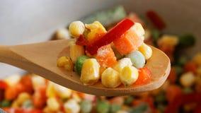 Zbliżenie łyżka z marznącymi mieszanymi warzywami zdjęcia royalty free