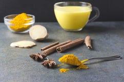 Zbliżenie łyżkowy pełny turmeric proszek, cynamon, filiżanka turmeric latte na tle, gwiazdowa annise, imbiru i szkła, składniki zdjęcia stock