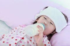 Zbliżenie śliczna azjatykcia dziewczyna z zimnem i grypa ssamy up dojną butelkę d zdjęcia stock