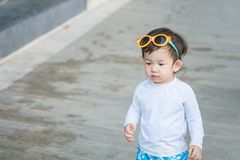 Zbliżenie śliczny azjatykci dzieciak w pływackim kostiumu z okularami przeciwsłonecznymi na jego głowa w lecie Thailand Zdjęcia Stock