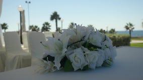 Zbliżenie ślubny bukiet białe leluje i białe róże dekorujemy tablecloth na plama kurortu pogodnym tle zbiory