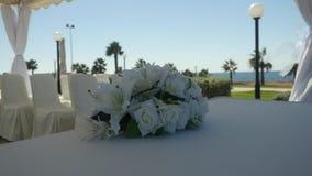 Zbliżenie ślubny bukiet białe leluje i białe róże dekorujemy tablecloth na plama kurortu pogodnym tle outdoors zbiory wideo