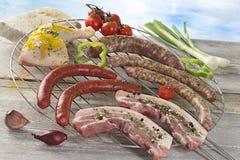 Zbliżenie świeży mięso i kiełbasy na grill siatce Zdjęcia Stock