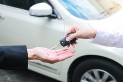 Zbliżenie żeński właściciel samochodu daje samochodów kluczom od samochodowego deale Obrazy Stock