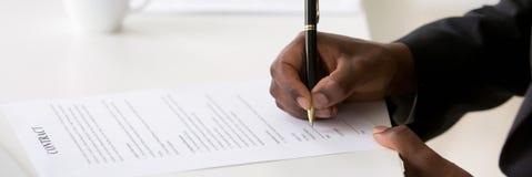 Zbliżenie afrykański biznesmen twierdzi kontrakt z podpisem wręcza chwyta pióro obrazy stock