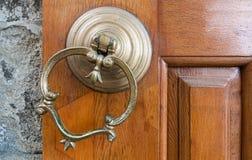 Zbliżenie antyka groszaka ozdobny drzwiowy knocker nad starzejącym się drewnianym drzwi fotografia royalty free
